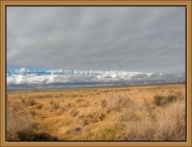 The Sierra Nevada Mountains peep trhough from clouds over the Owens Valley. The High Sierra contains a string of the highest mountains in the contiguous United States, among the m Mt. Whitner.